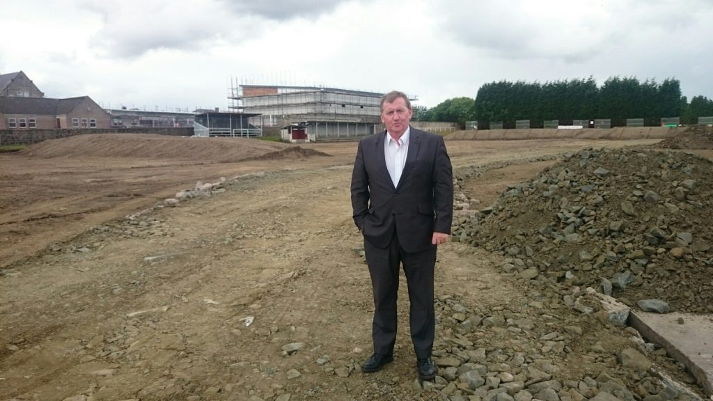Alex Rowley viewing the ground works with the towering games hall in the background